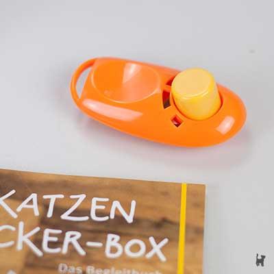 Orangefarbener Clicker mit gelbem Knopf