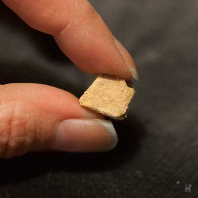 Zwei Finger halten einen Cosma Snackie