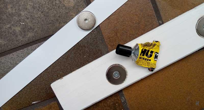 In Holzlatten eingeklebte runde Magnete